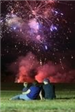 Family gazing at fireworks at night